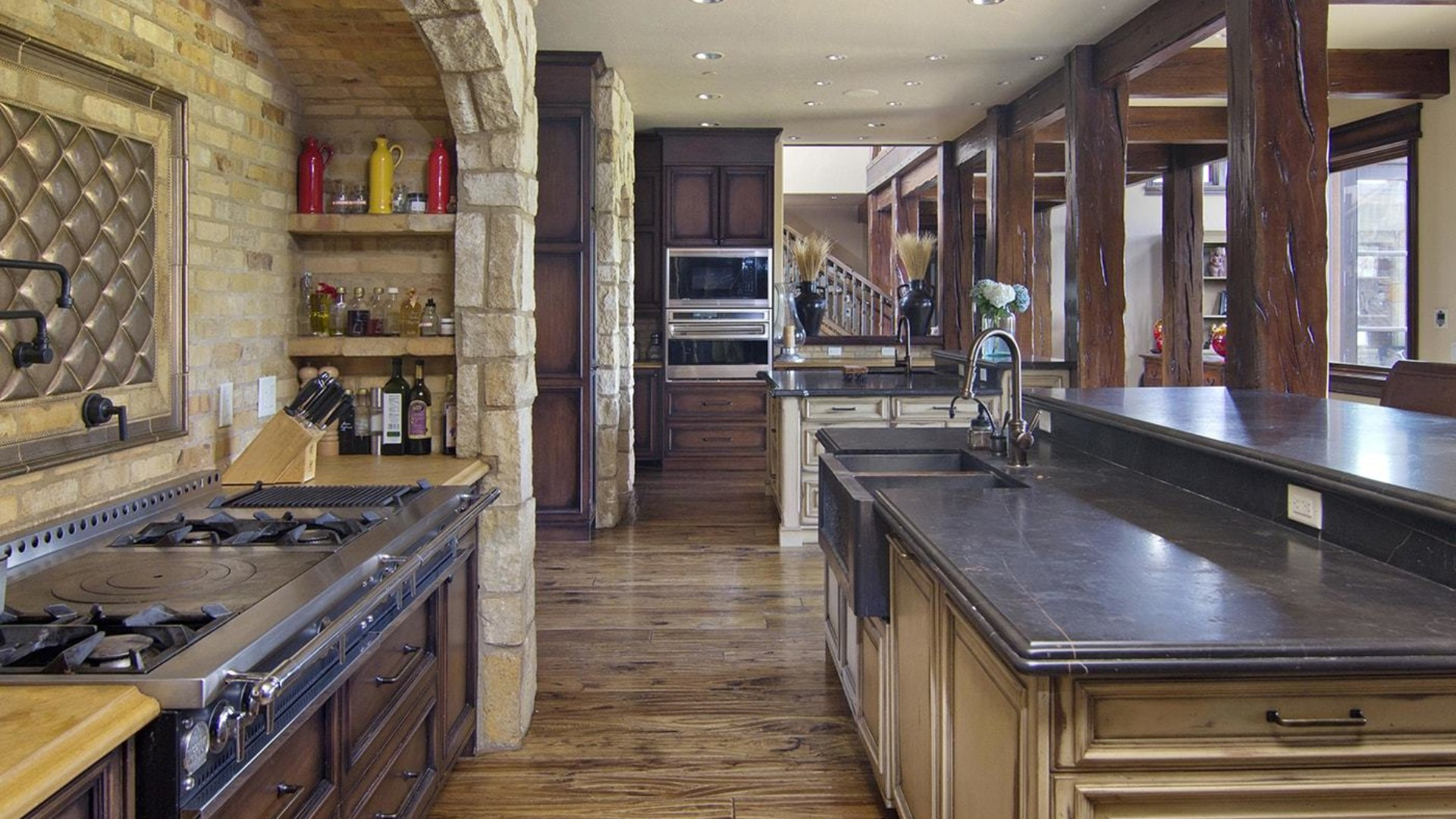 the kitchen of a jackson hole, wyoming mansion with dark granite countertops and rustic interior