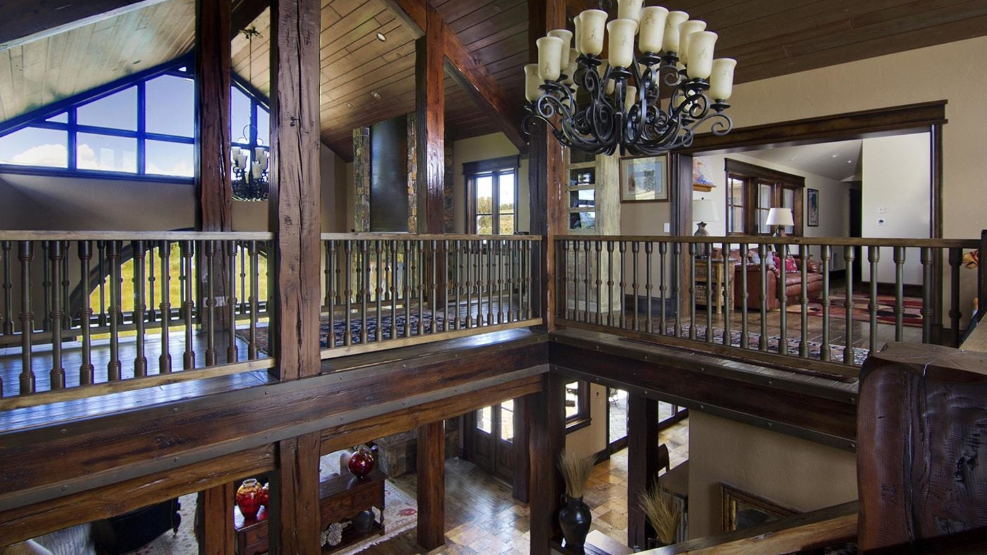 wide view of a rustic mansion upstairs loft area with wooden beams, large windows and a chandelier