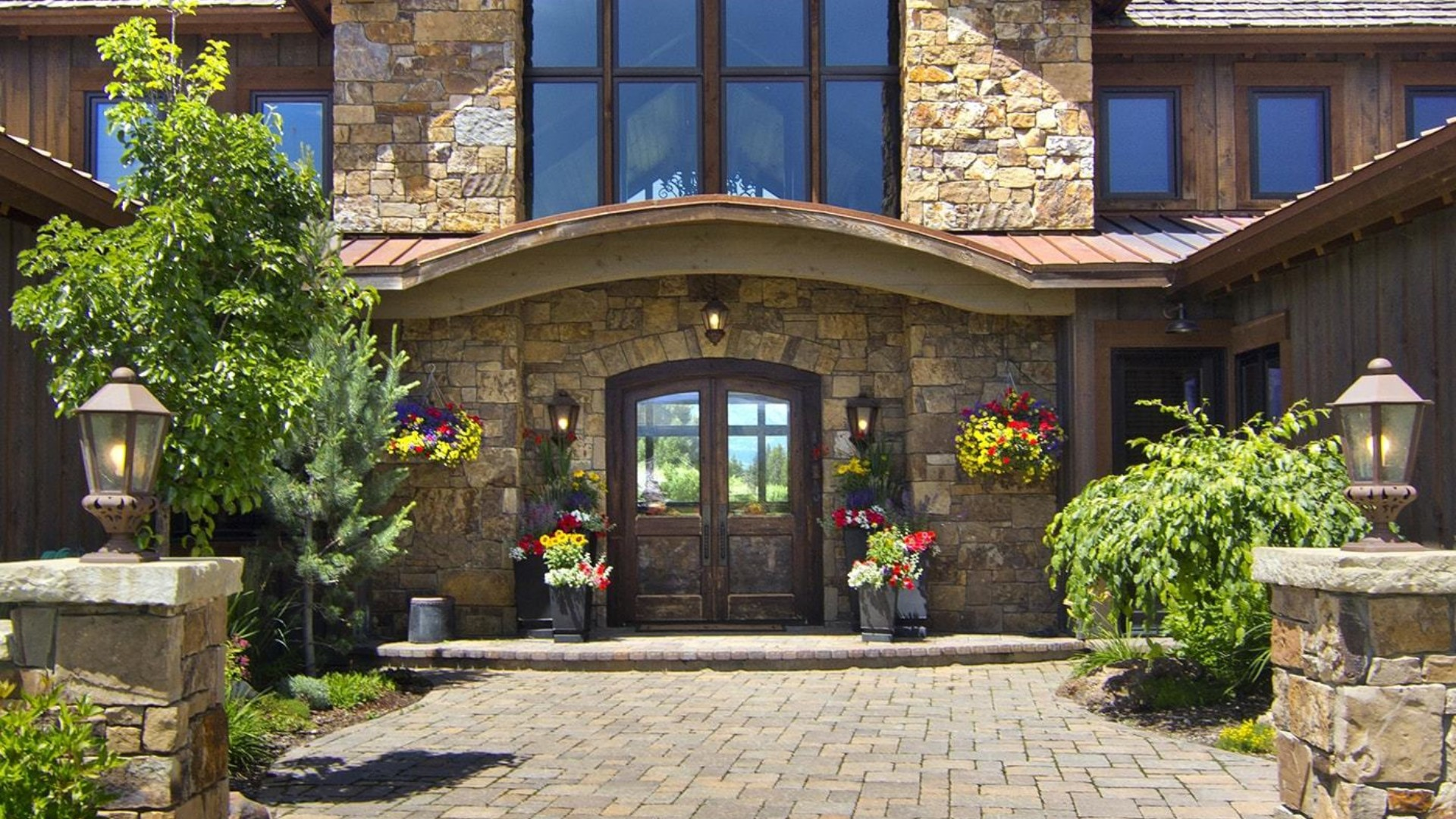 front view of stone brick mansion, stone walkway and landscaping in jackson hole wyoming
