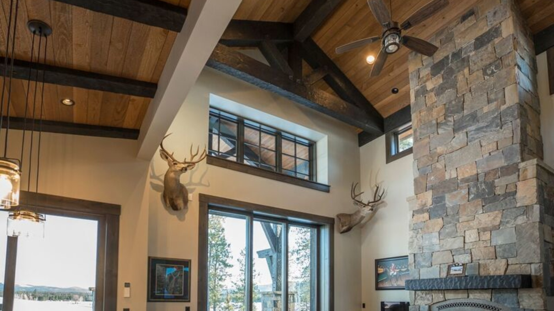 wooden ceiling with large dark brown wood trusses and a stone fireplace